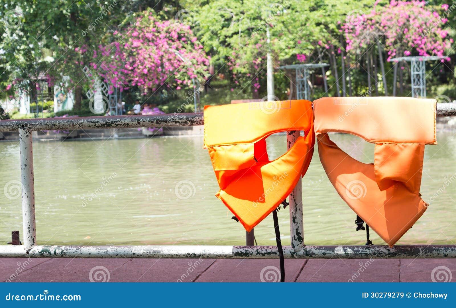 在篱芭烘干的橙色生活安全夹克