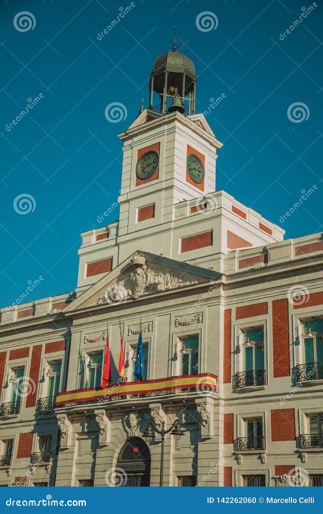 在精妙的老大厦与钟楼和时钟的旗子在马德里