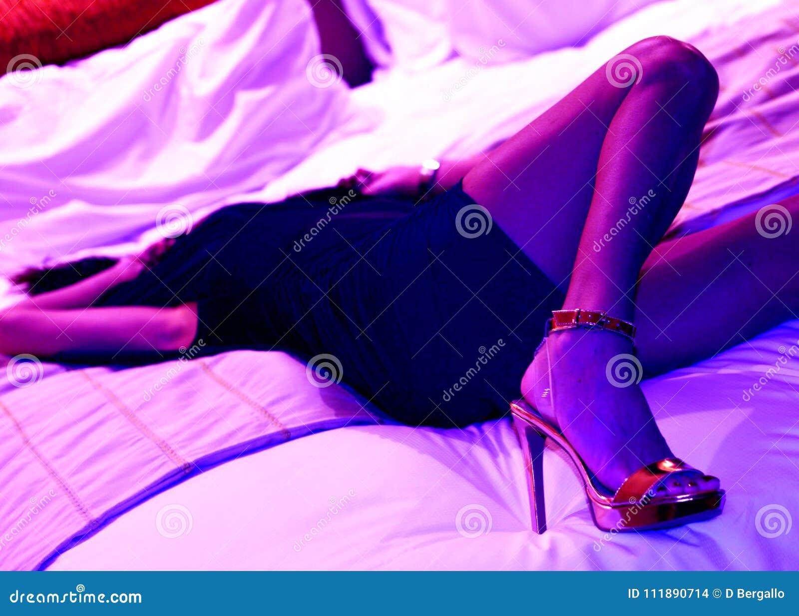 在紫色紫外光华美的腿的美好的模型在高跟鞋