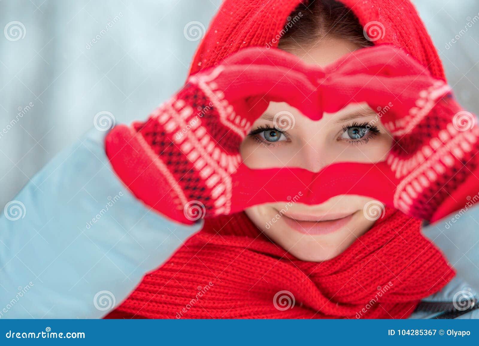 在红色冬天手套的妇女手 心脏标志形状的生活方式和感觉概念