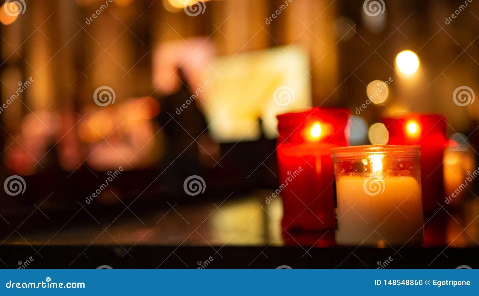 在红色和白色玻璃的纪念蜡蜡烛在教会里
