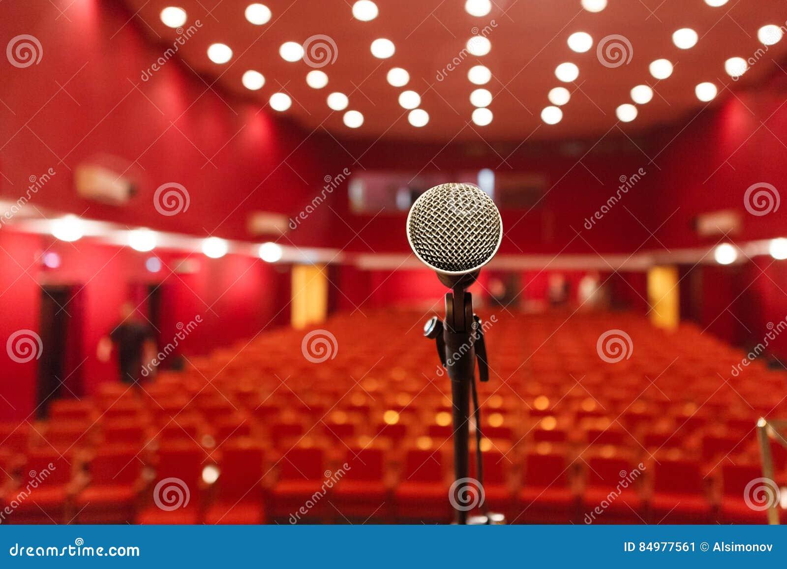 在红色大厅背景的话筒有就座的观众的
