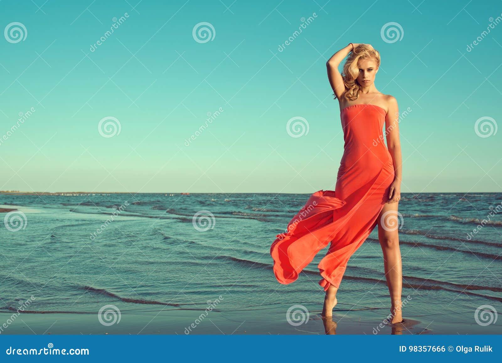 在红色无背带的礼服的华美的性感的微小的白肤金发的模型有热切站立在海水的飞行火车的
