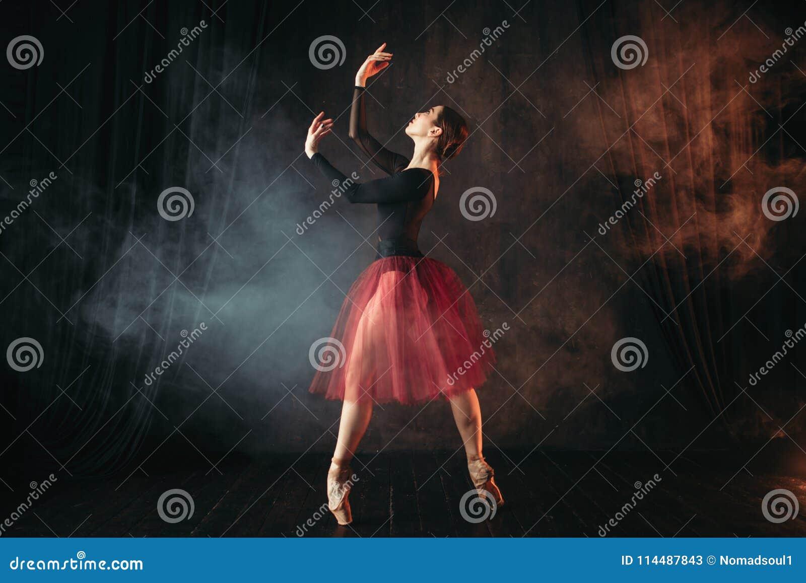 在红色礼服跳舞的跳芭蕾舞者在阶段