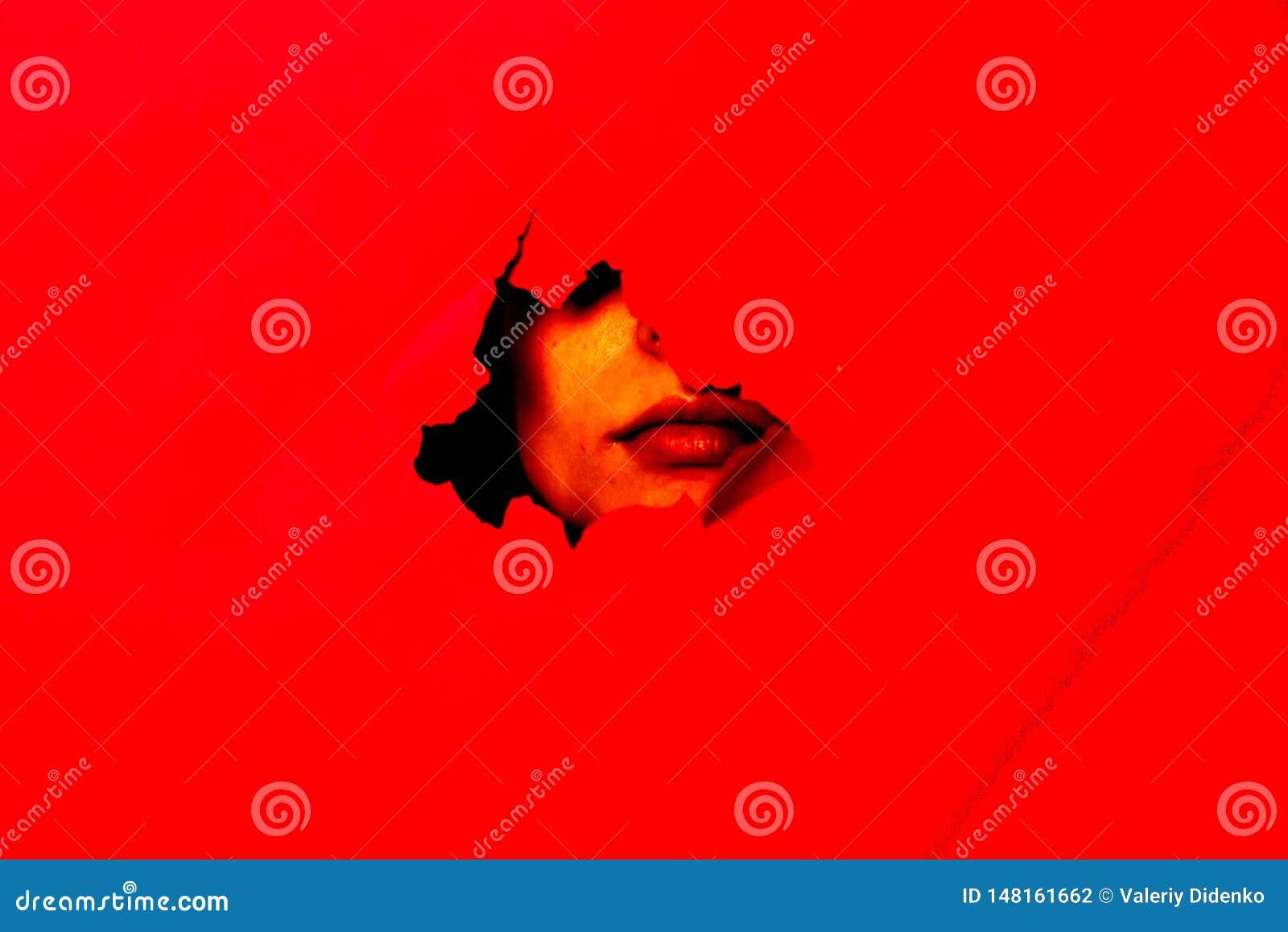 在红色背景,面孔在孔能被看见