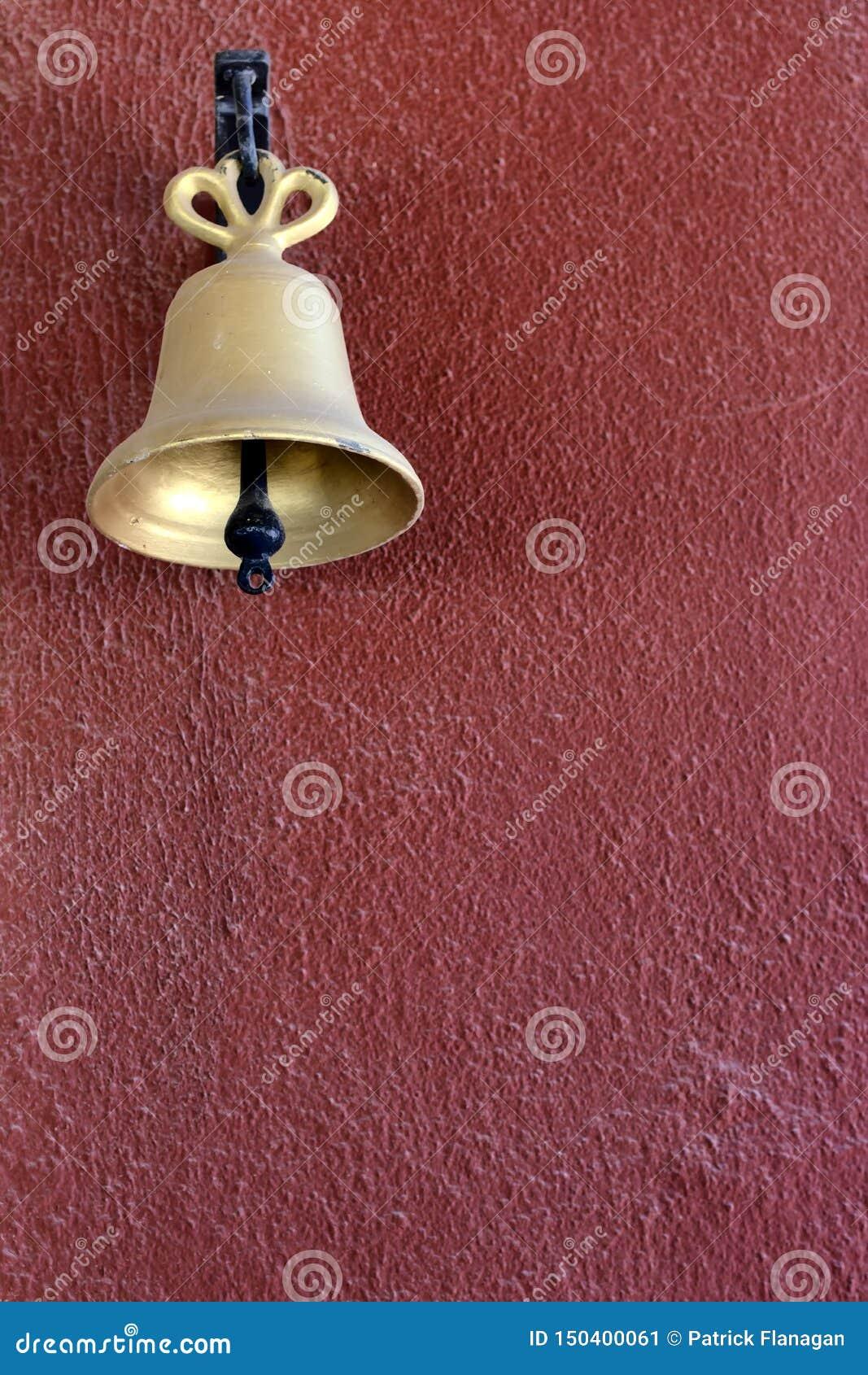 在红色被绘的墙壁上的金响铃