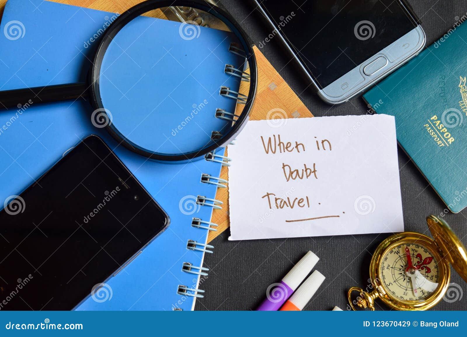 在纸写的当不确定时旅行 护照,放大镜,指南针,智能手机