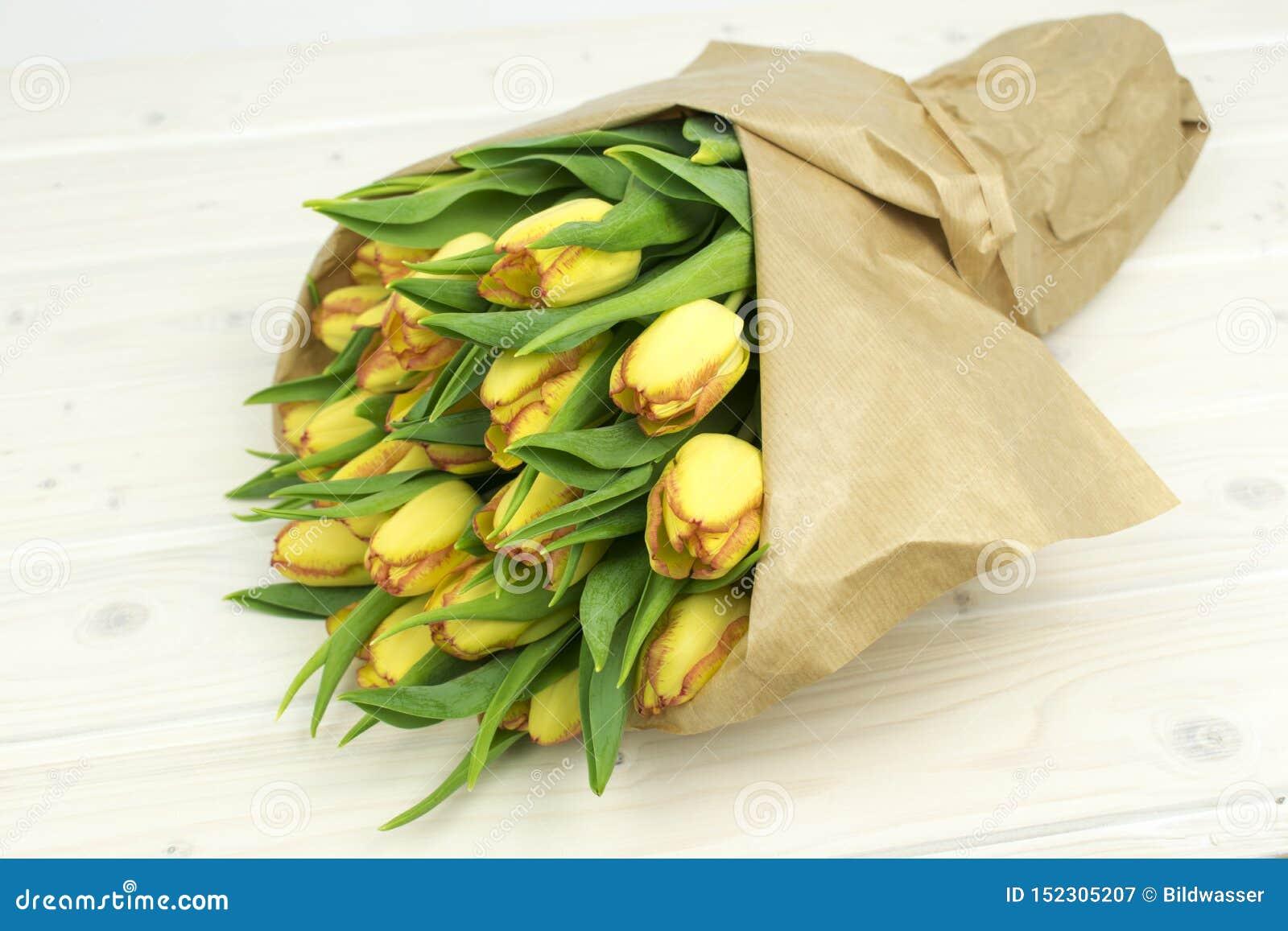 在纸花束的郁金香在木桌上