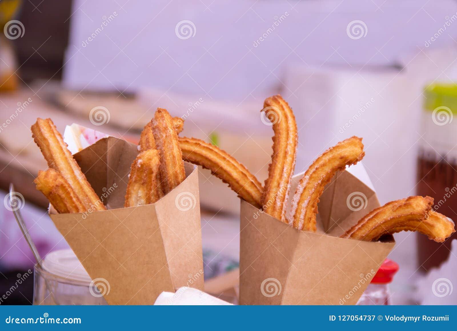 在纸袋油炸的可口churros棍子用搽粉的糖