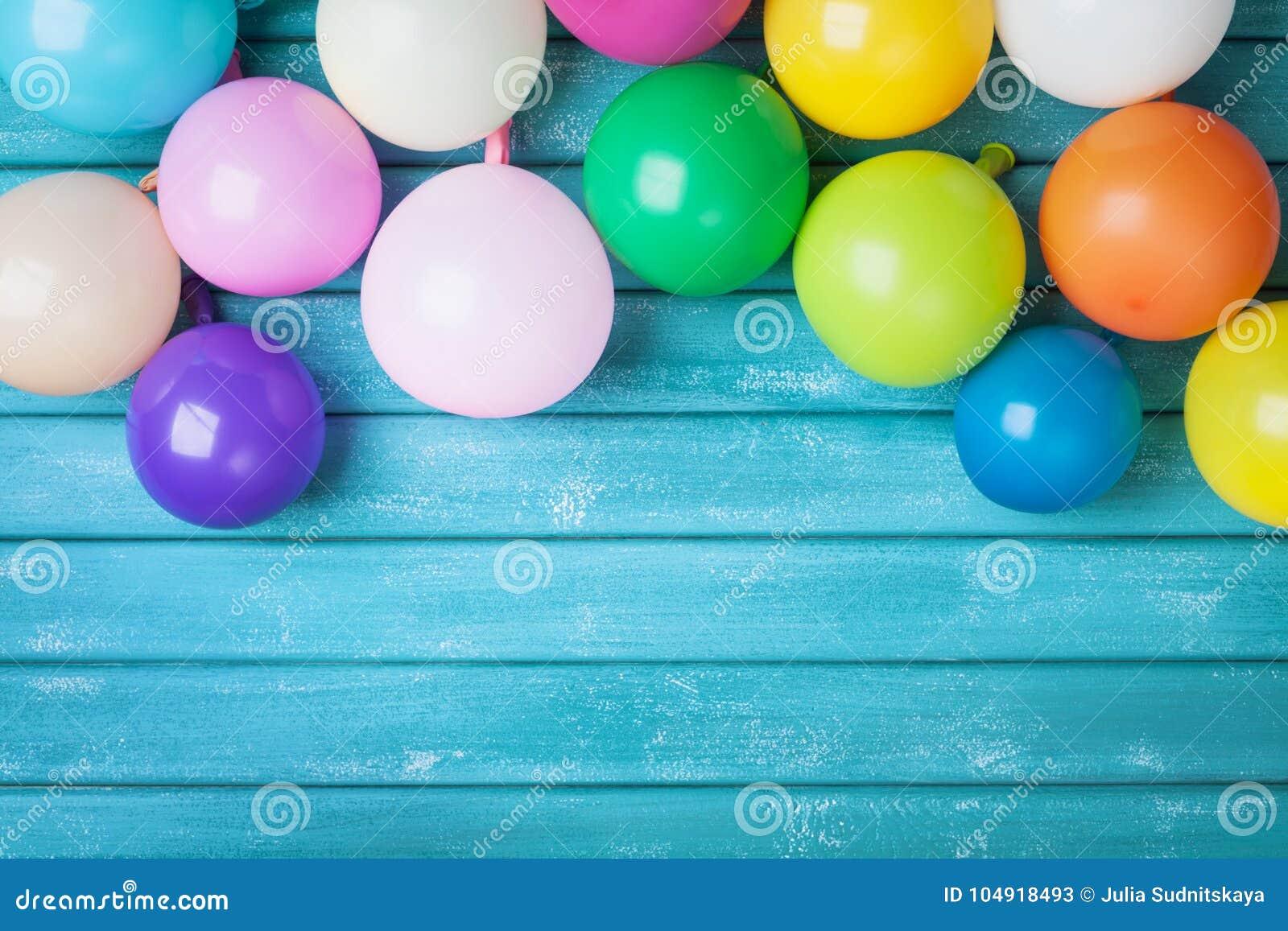 在绿松石木台式视图的五颜六色的气球 生日庆祝或党背景 欢乐贺卡