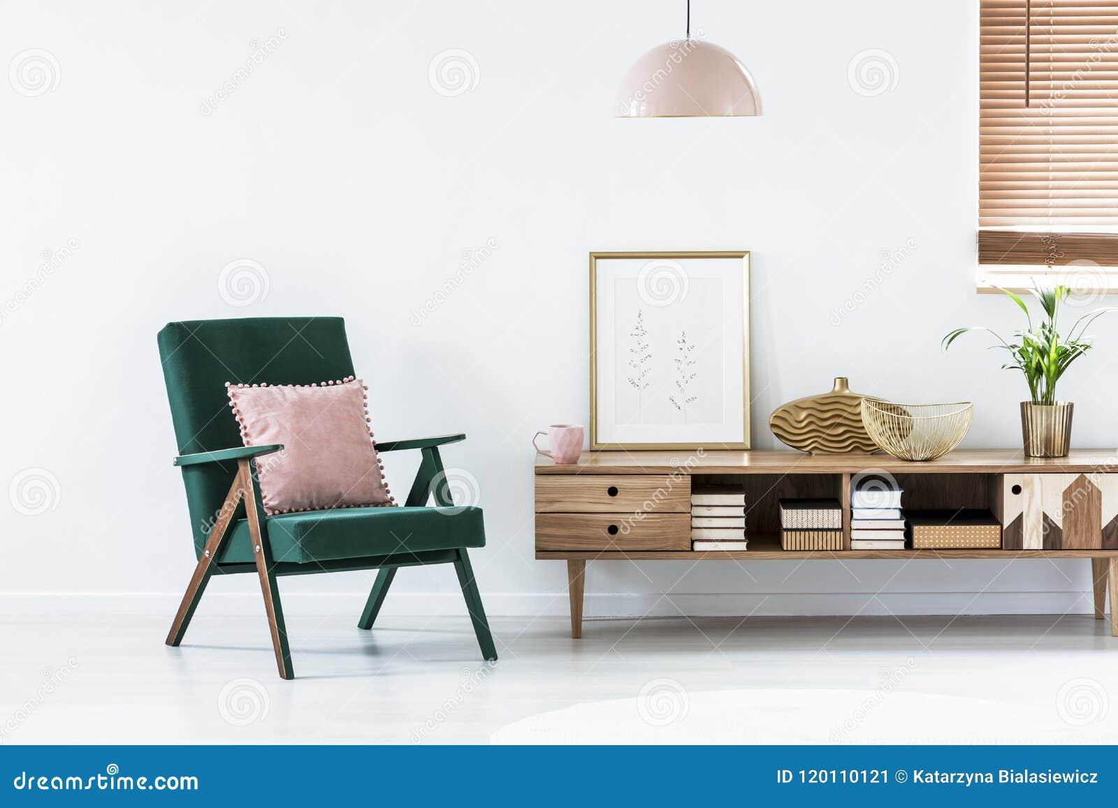 在绿色扶手椅子的桃红色枕头在livin的土气碗柜旁边