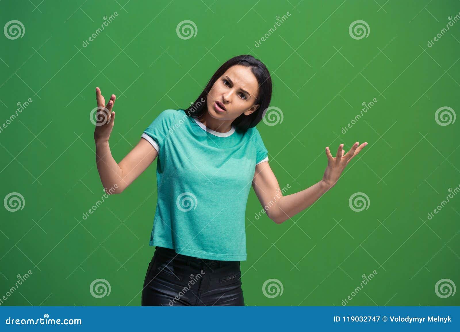 在绿色演播室backgroud隔绝的美丽的女性半身画象 年轻情感惊奇的妇女