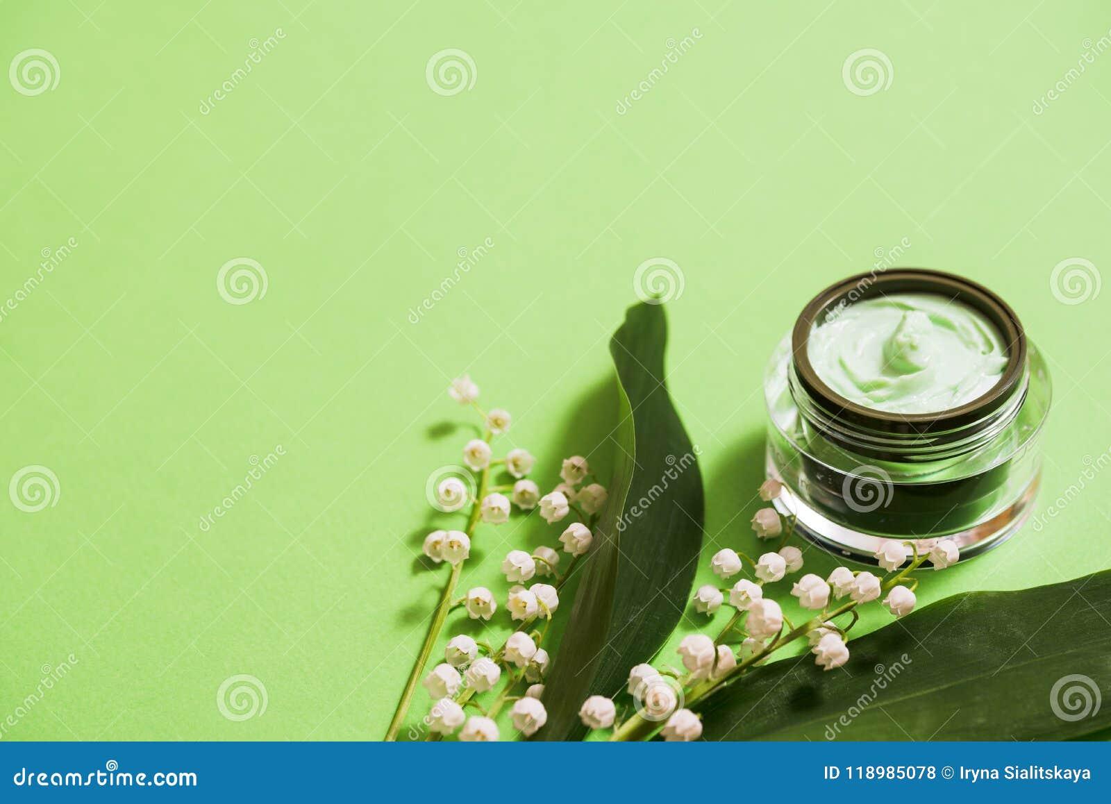 在绿色背景的化妆奶油和铃兰花