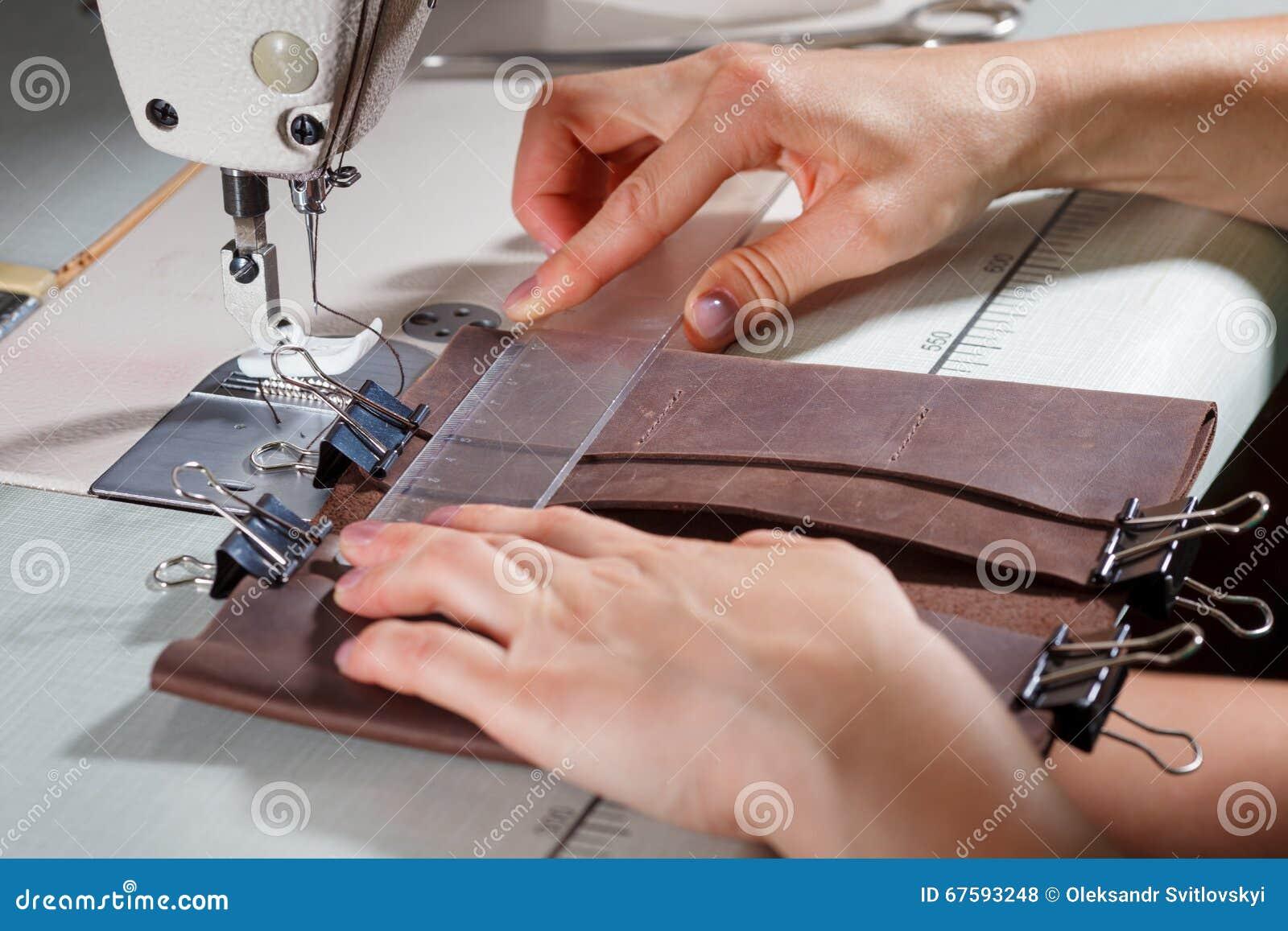在缝纫机的妇女的手