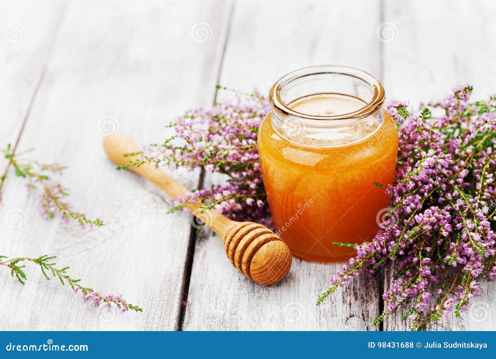 在罐或瓶子和花石南花的新鲜的蜂蜜在木葡萄酒桌上 复制文本的空间