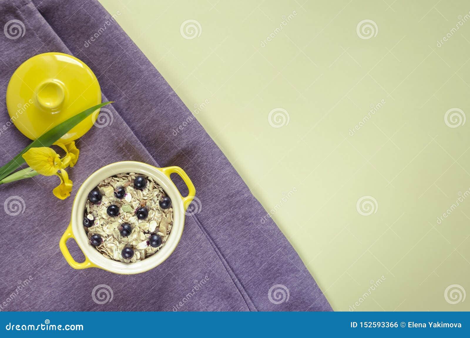 在罐的燕麦粥,muesli用新鲜的蓝莓和无核小葡萄干 装饰的黄色虹膜在紫色