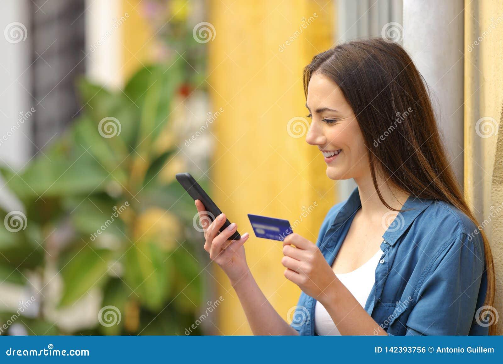 在网上支付使用信用卡的愉快的妇女