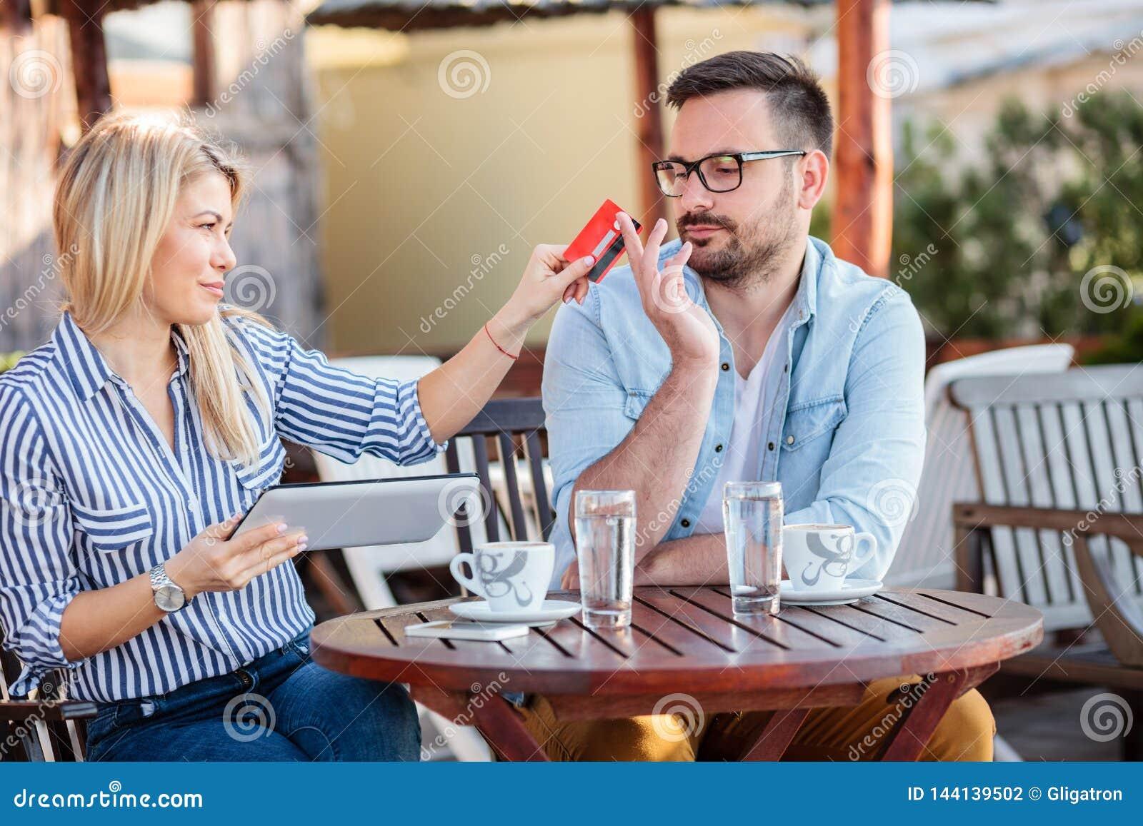 在网上购物愉快的年轻的夫妇坐在咖啡馆和