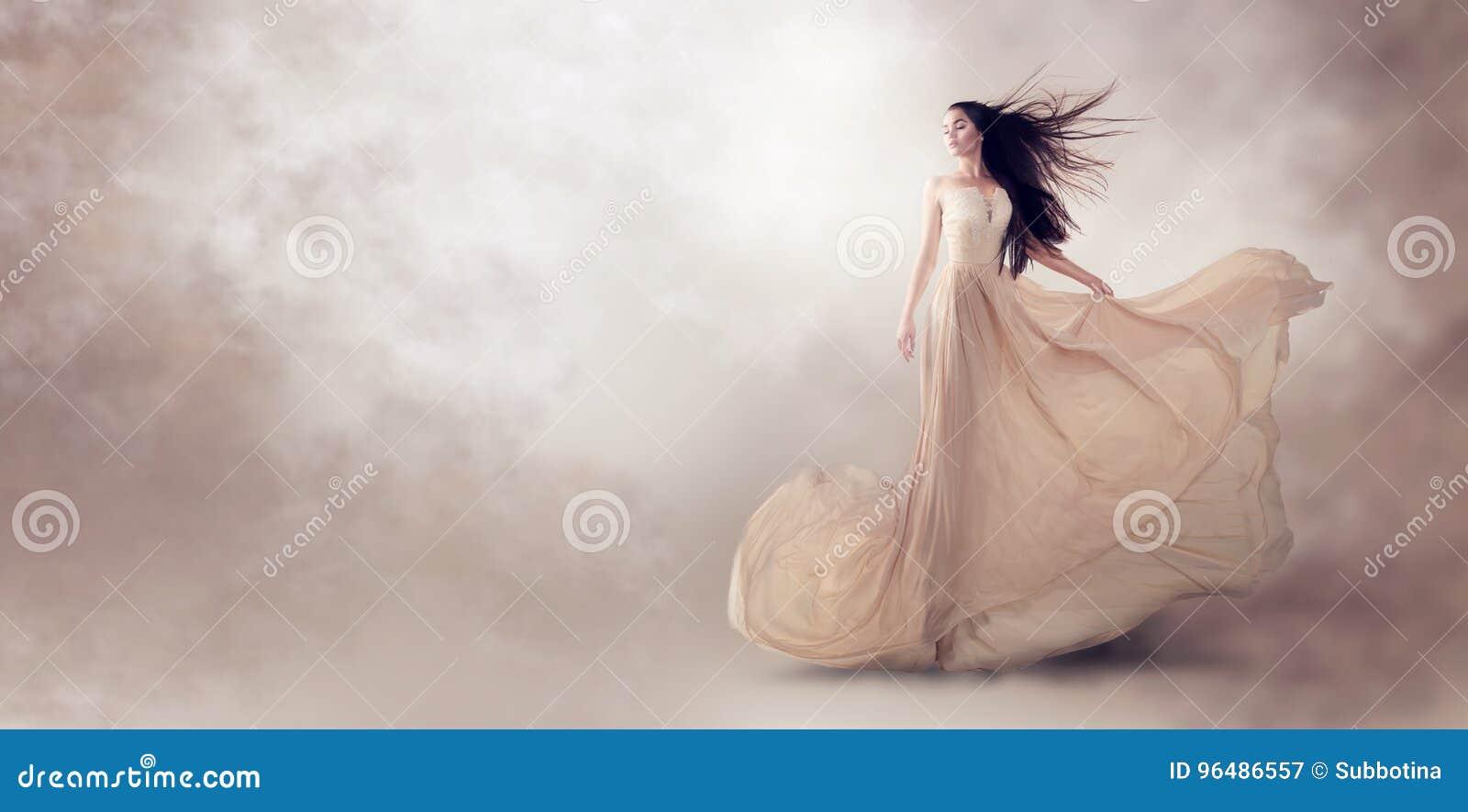 在美丽的米黄流动的薄绸的礼服的时装模特儿