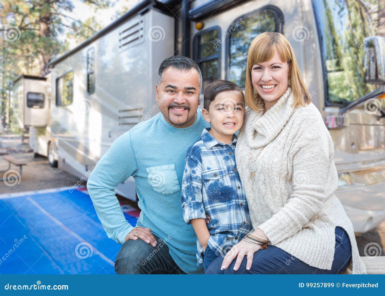 在美丽的RV前面的愉快的年轻混合的族种家庭