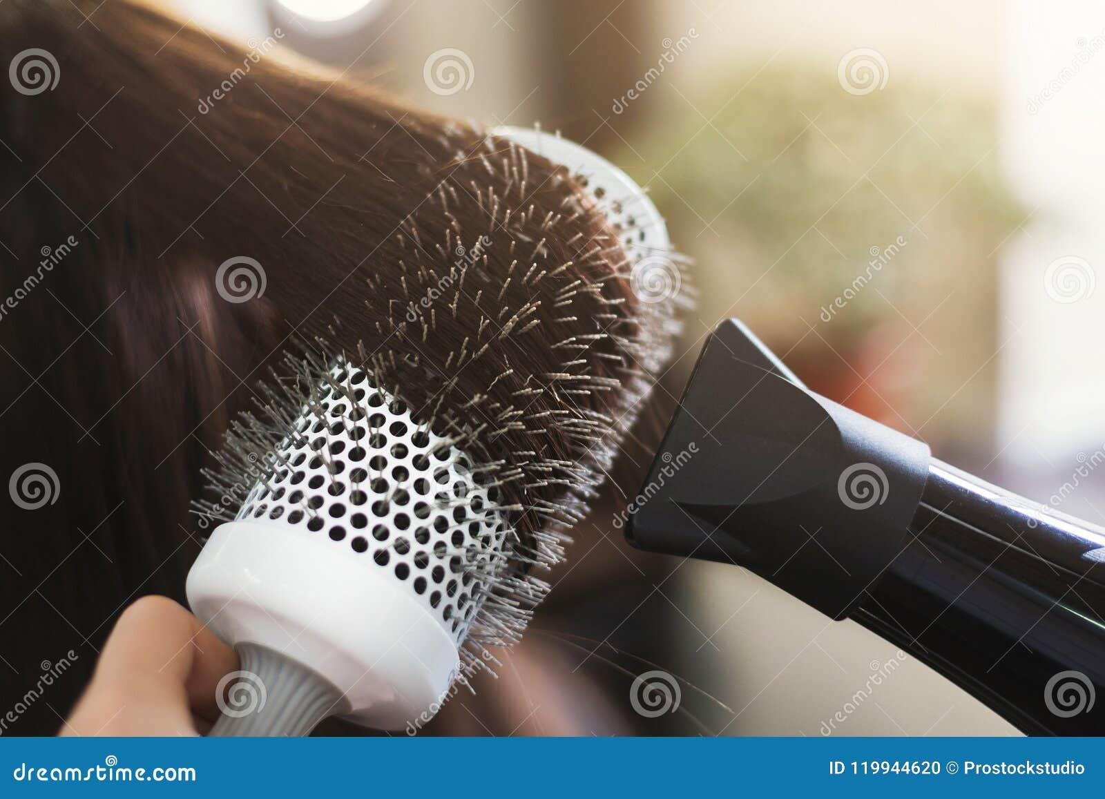 在美容院的美发师干燥妇女` s头发