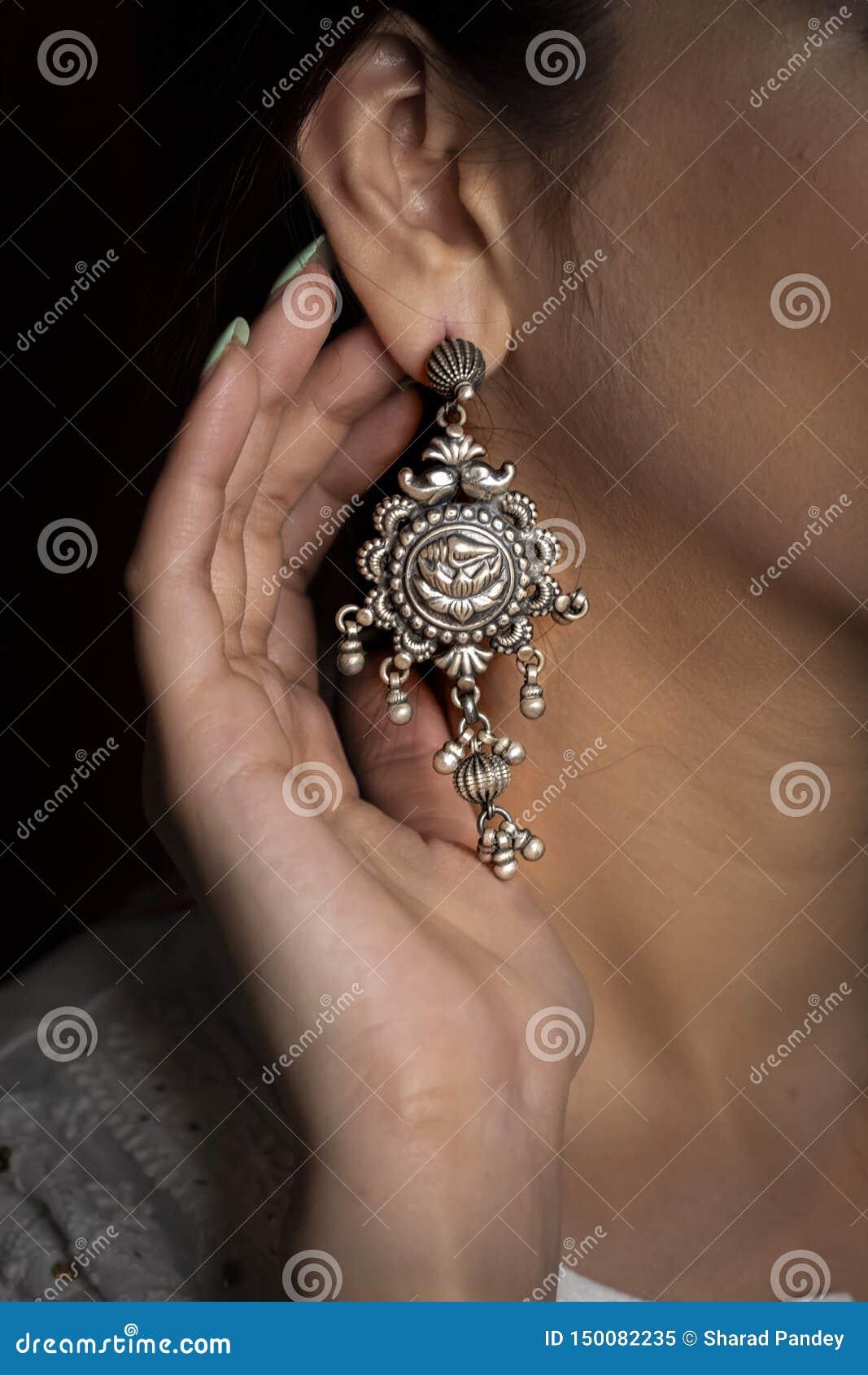 在耳朵的妇女佩带的银色耳环有手陈列的