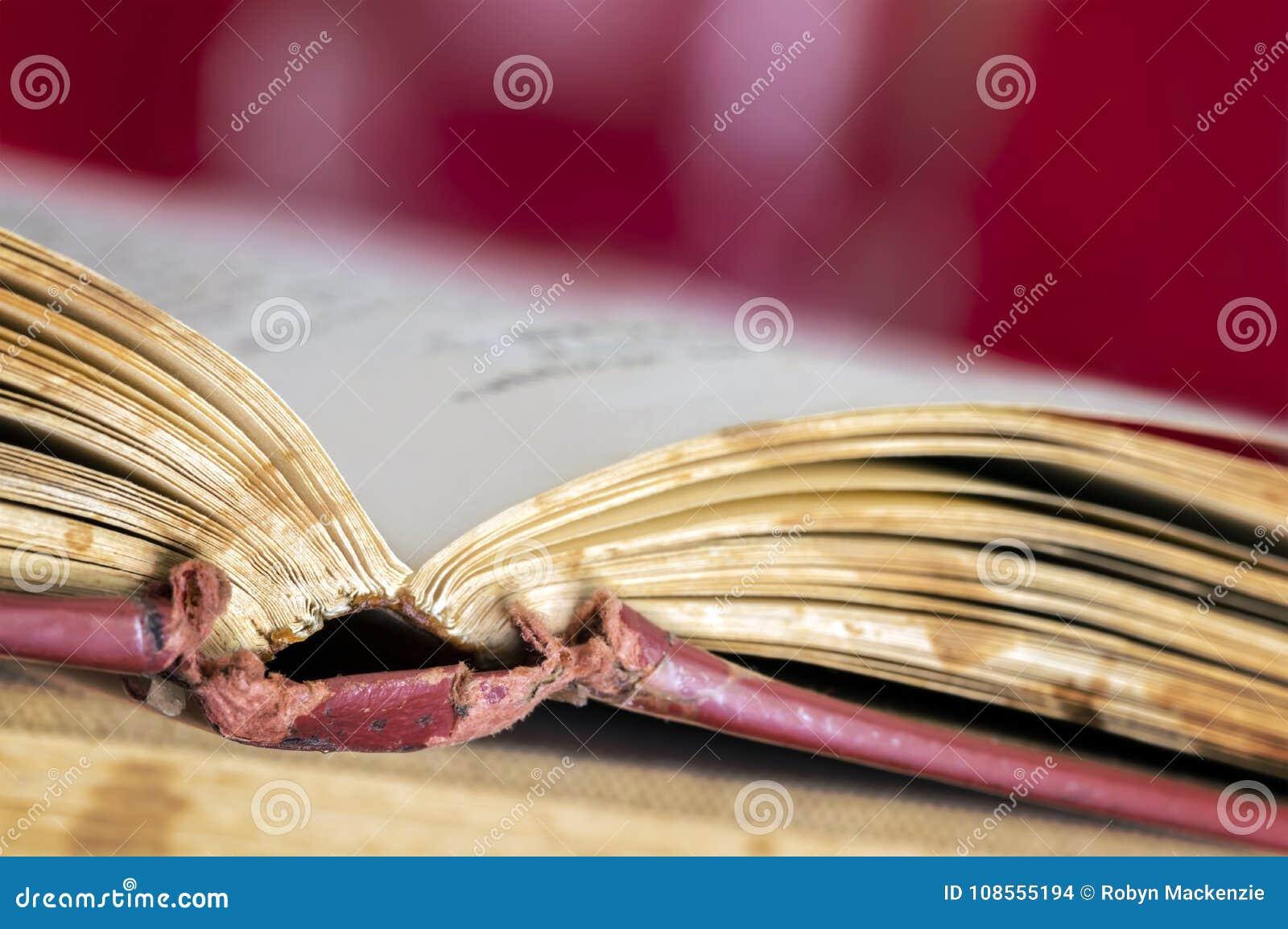 在脊椎被弄脏的背景的旧书开放焦点
