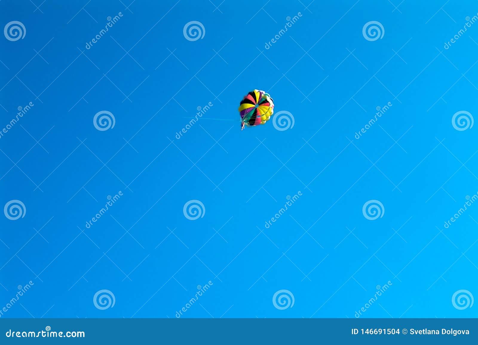 在色的降伞的跳伞运动员飞行在蓝色清楚的天空