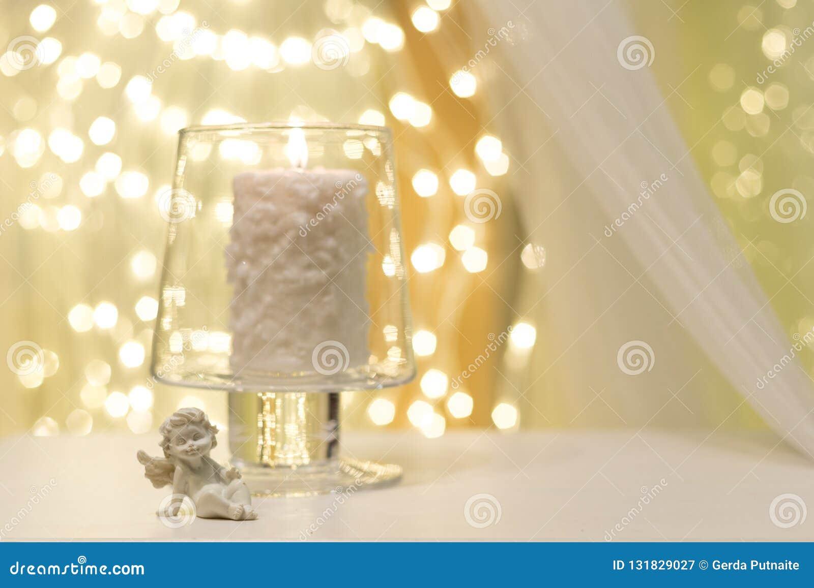 在花瓶的燃烧的蜡烛有在它旁边的一个天使形象的