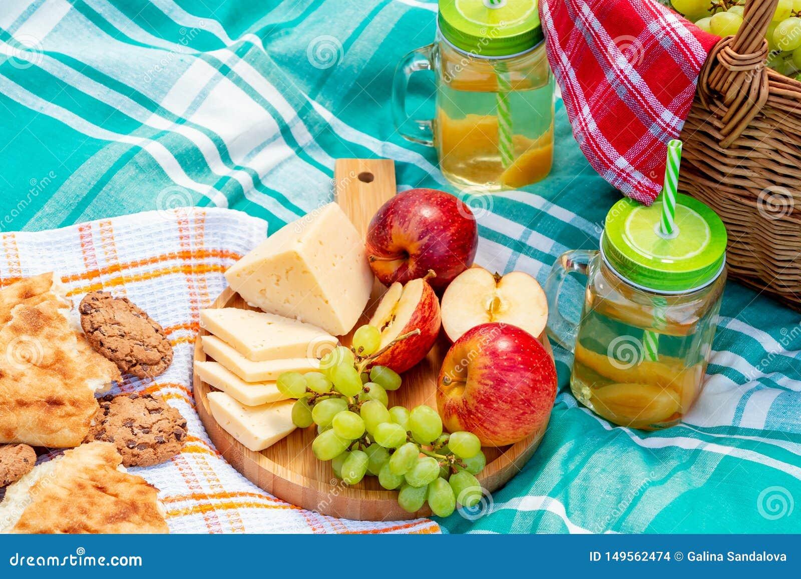 在草在一个夏日-篮子,葡萄,乳酪,面包,苹果的野餐-夏天室外休闲的概念