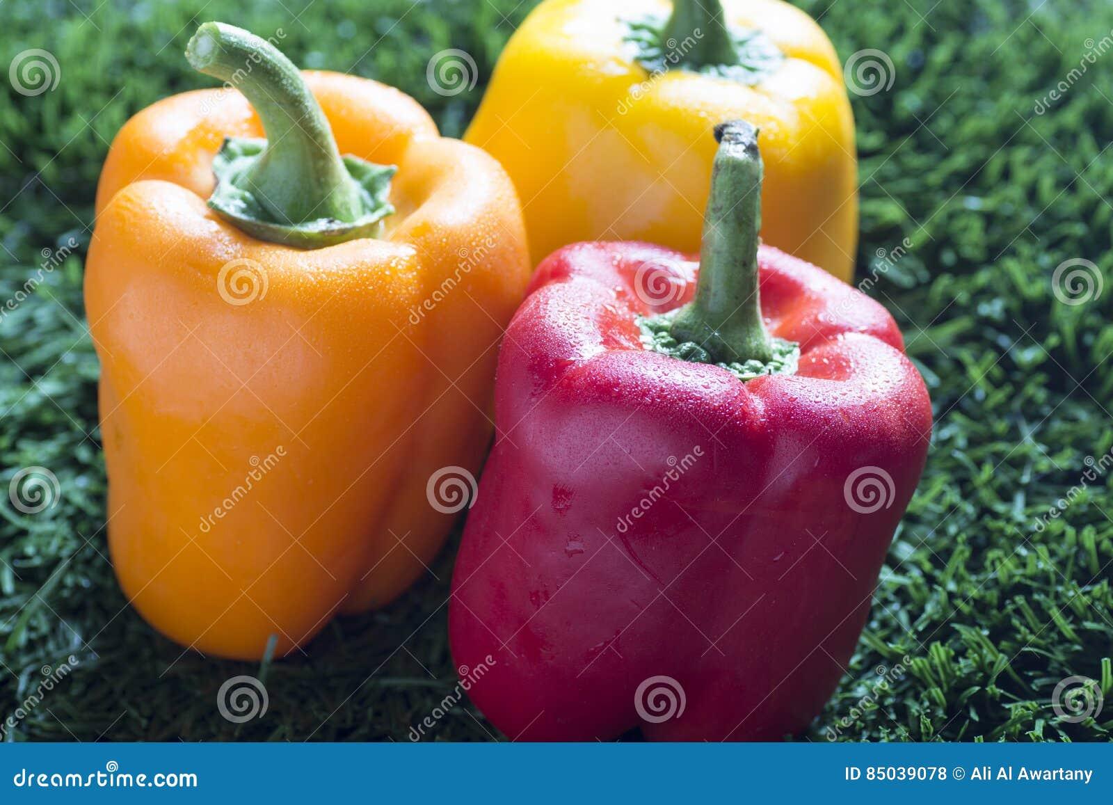 在草的红色,黄色和橙色辣椒粉用水滴下