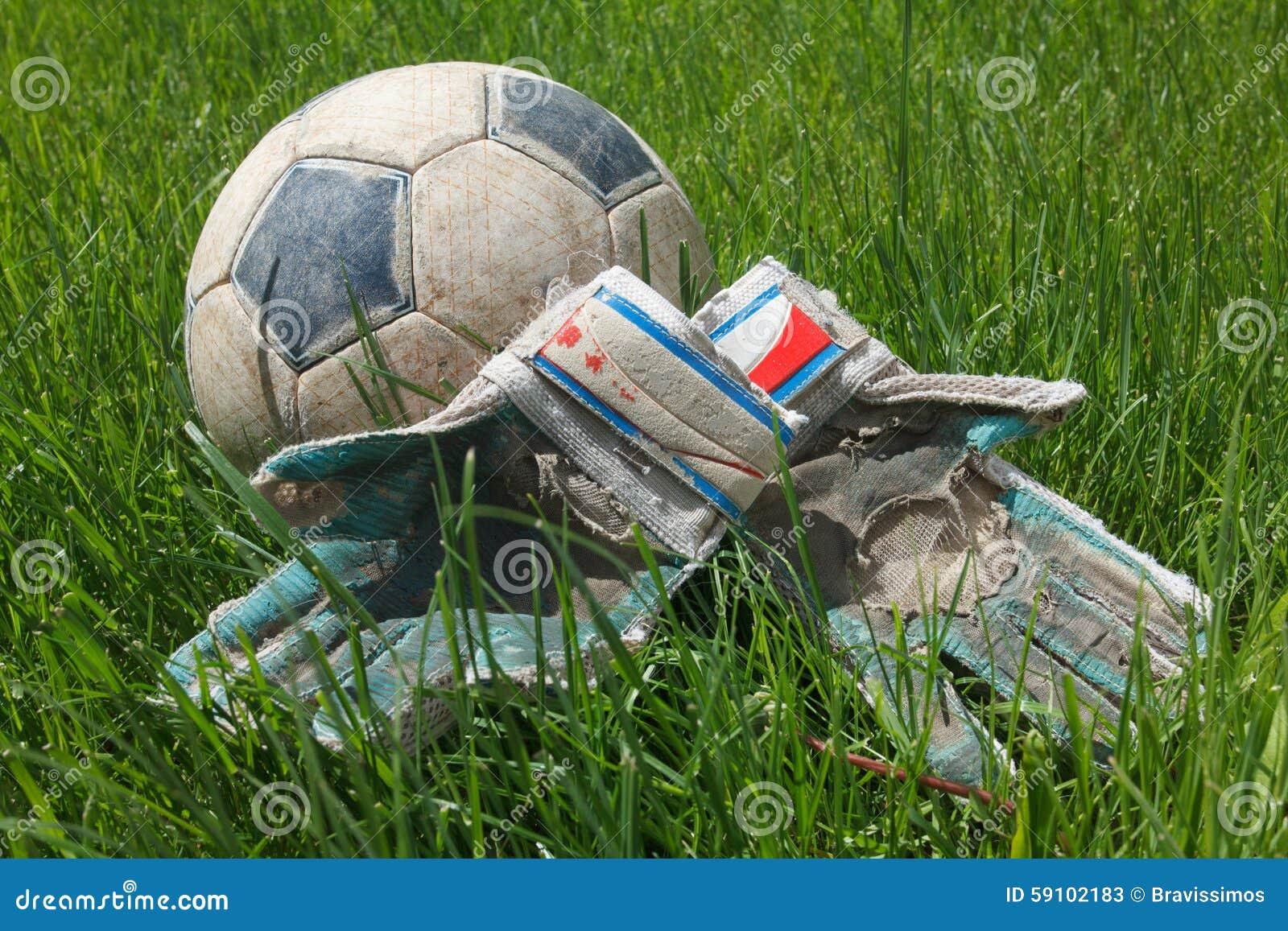 在草的足球和守门员手套