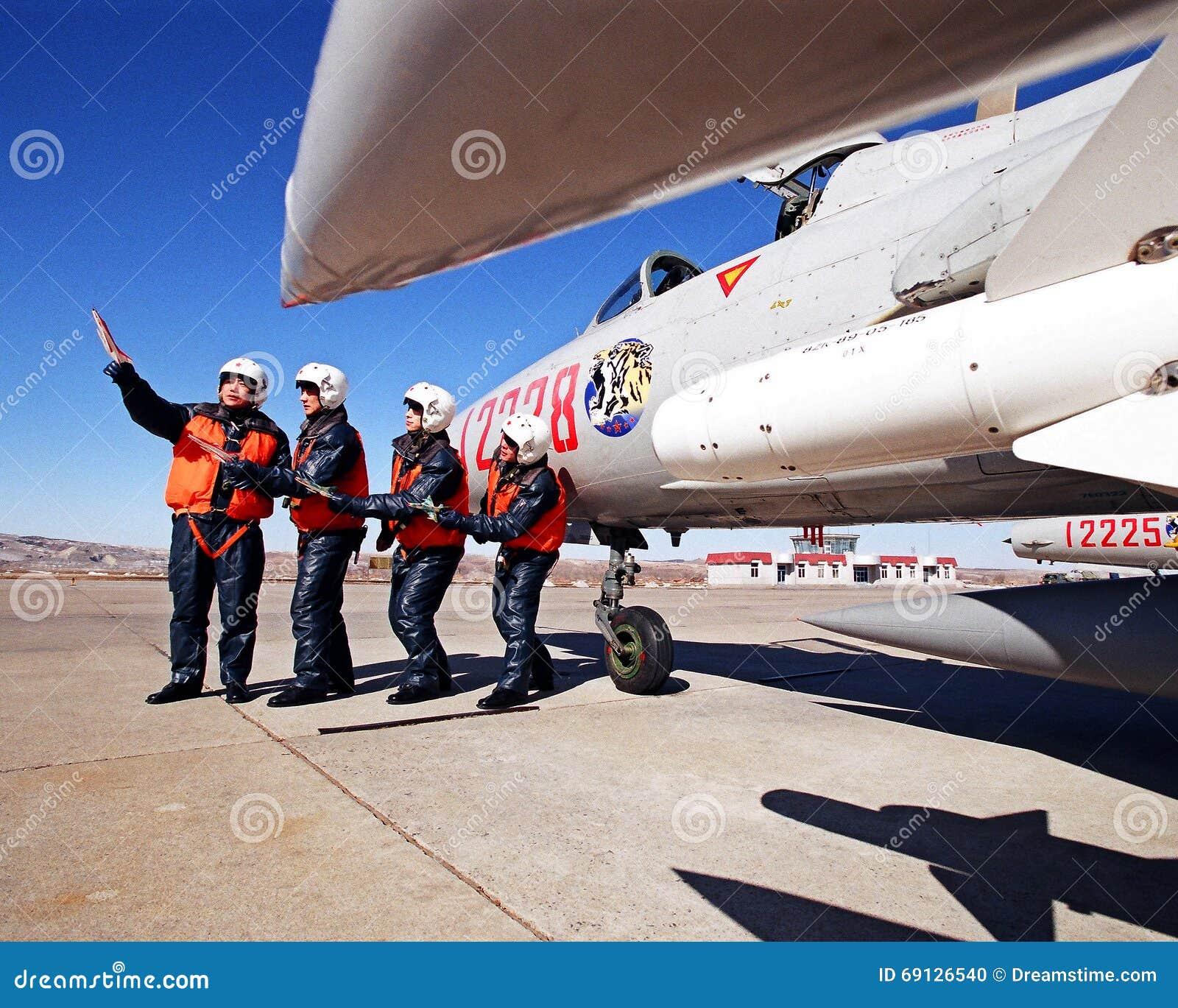 在蓝天下,一个军事机场,四在战斗机八航空器飞行模仿训练旁边的飞行员