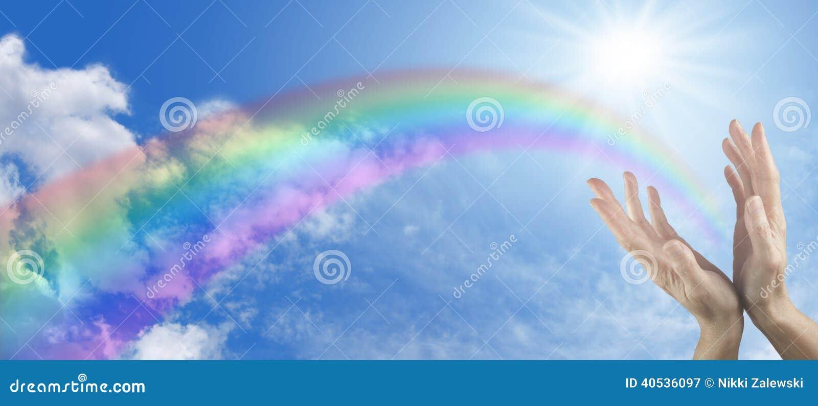 在蓝天和彩虹横幅的医治用的手