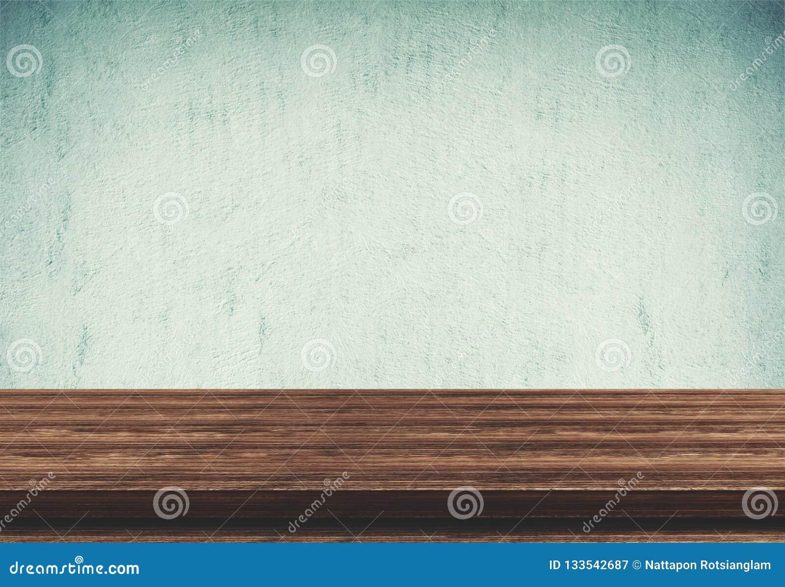 在蓝色具体背景的空的木台式