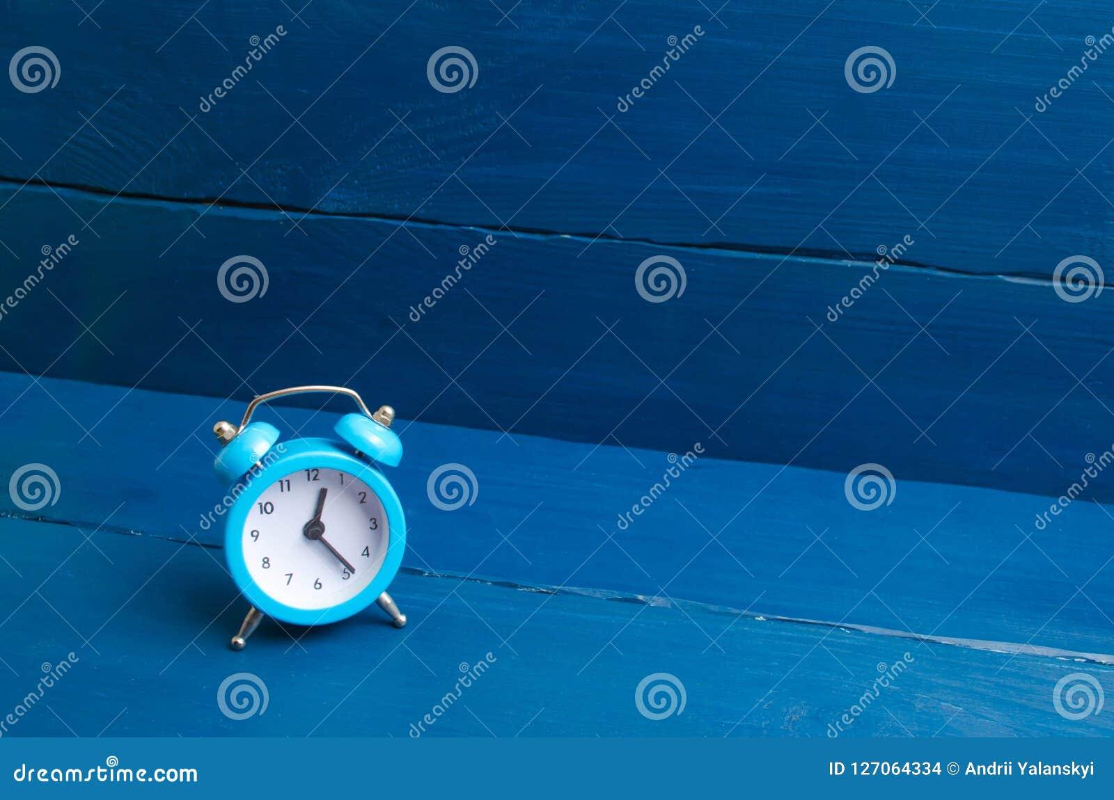 在蓝色木背景的蓝色闹钟 时间的概念 几小时的翻译冬天或夏时的