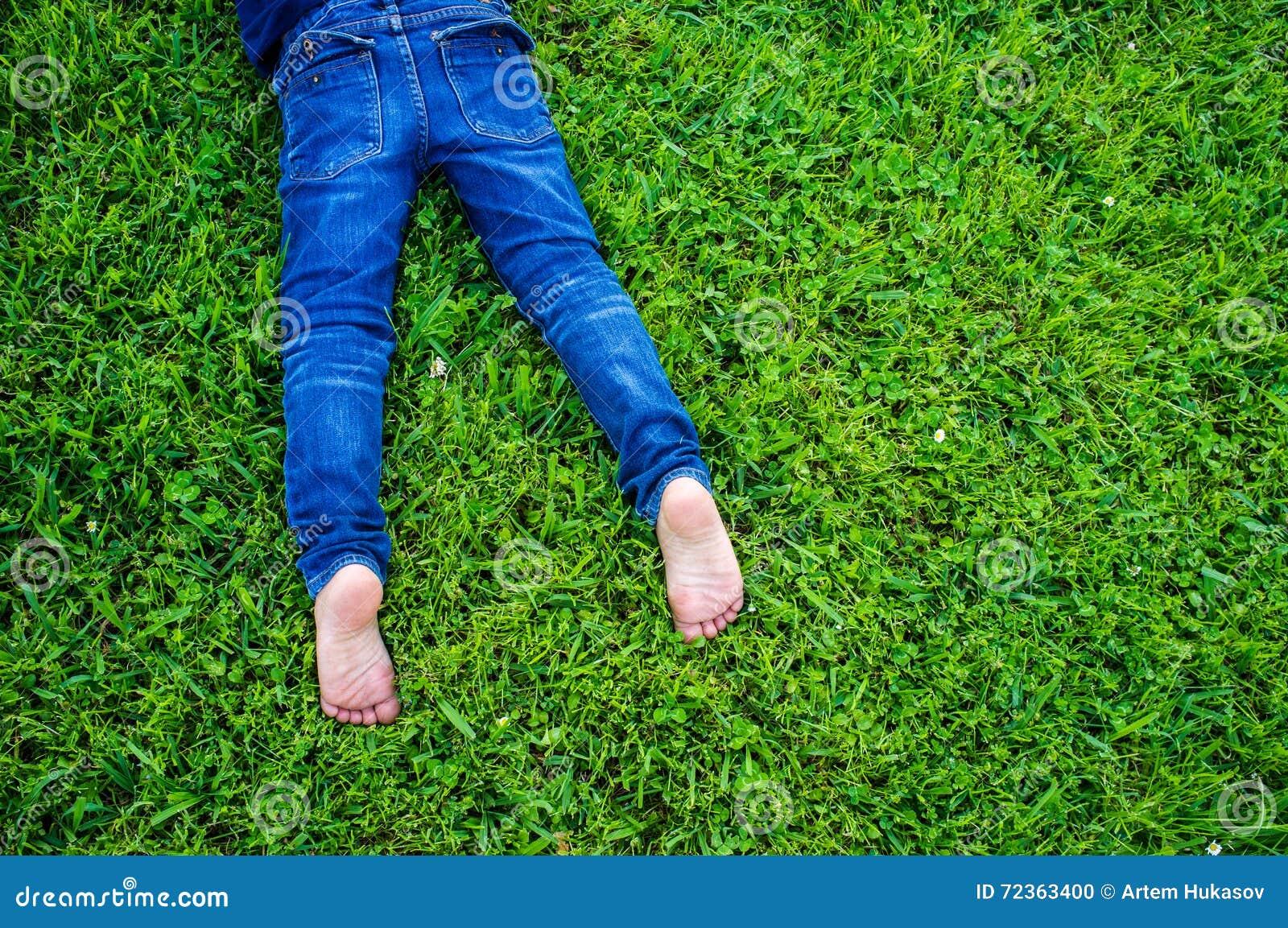 在蓝色牛仔裤的儿童的赤脚