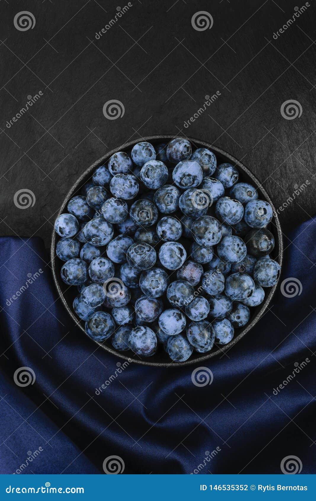 在蓝色织品和黑石背景的蓝莓