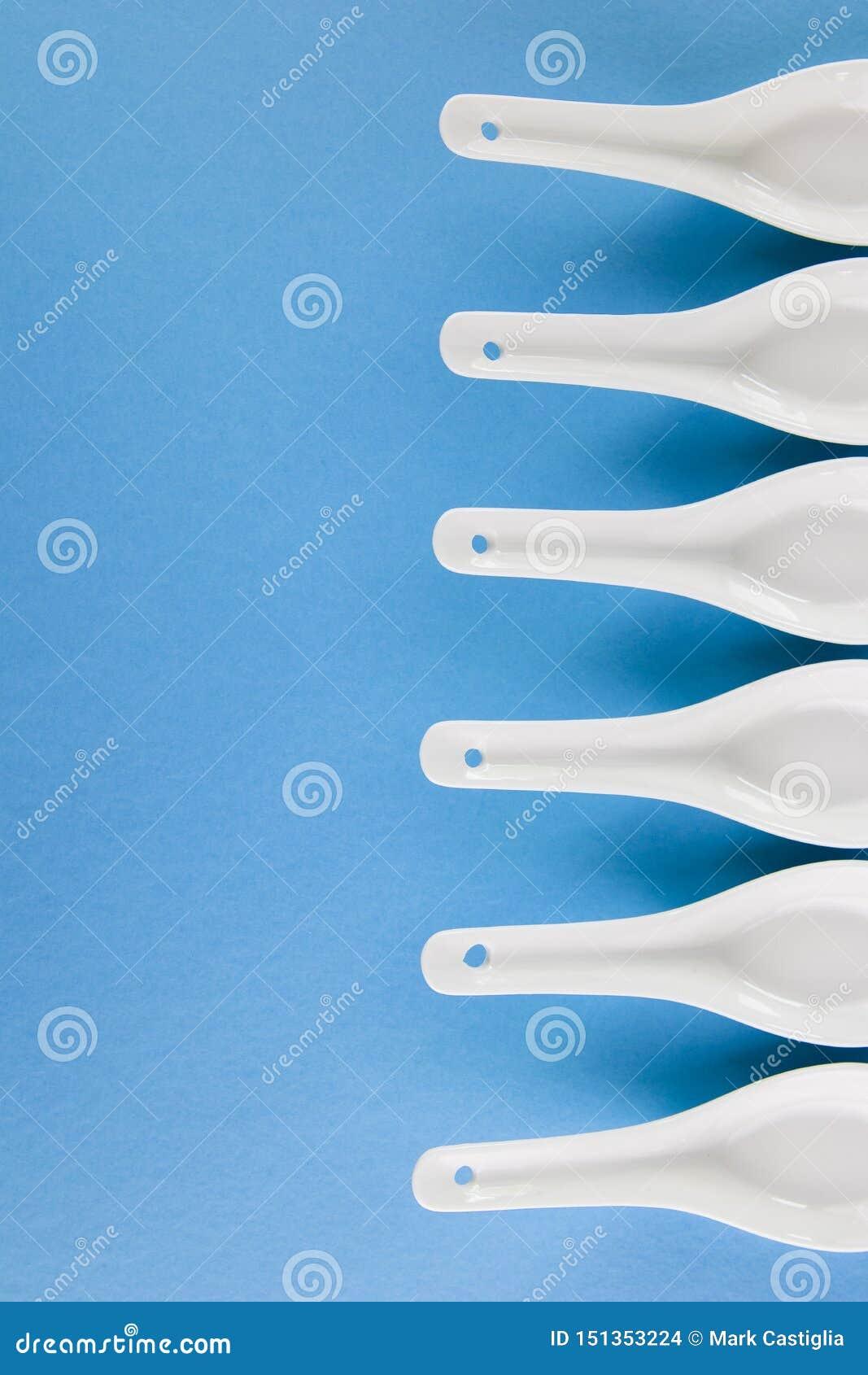 在蓝色背景的一个抽象样式安排的白色亚洲样式匙子