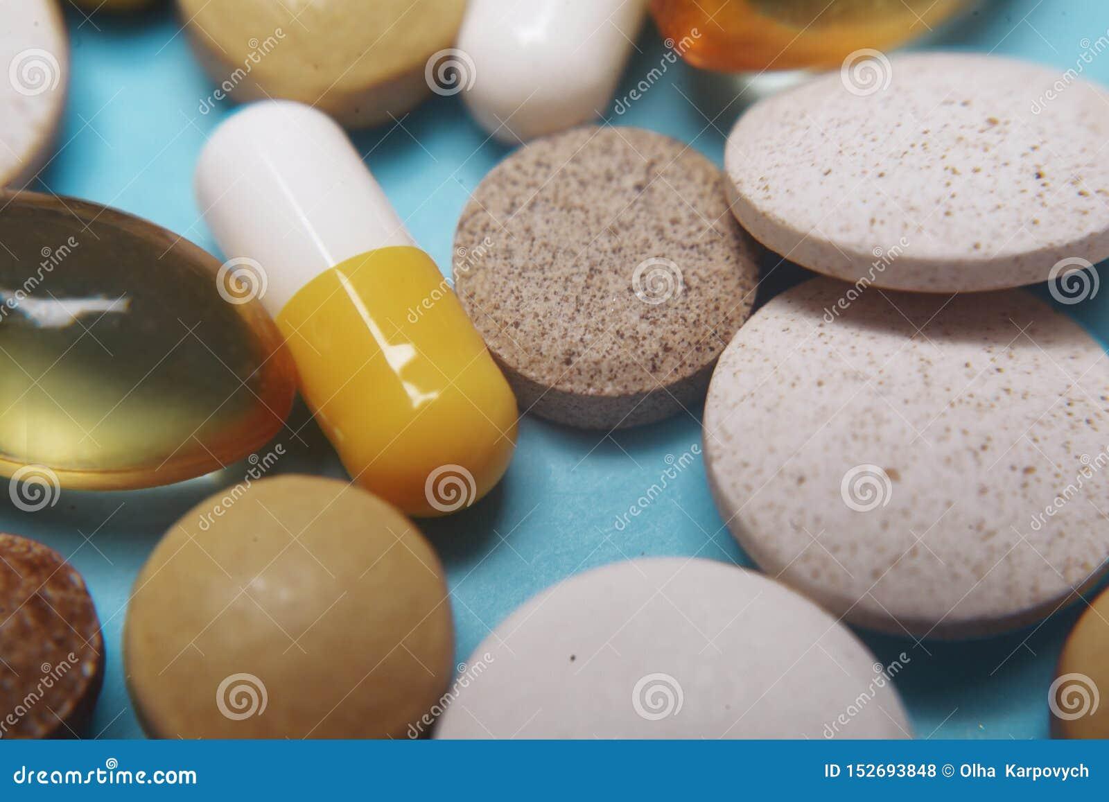 在蓝色背景的药片 被分类的配药医学药片、片剂和胶囊,健康宏指令 各种各样的药片堆