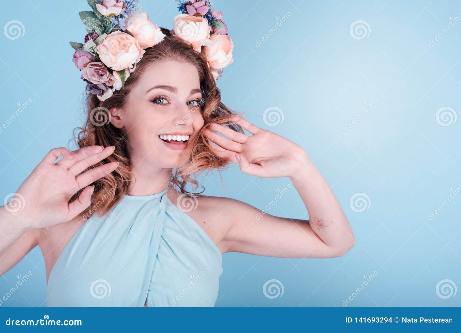在蓝色背景隔绝的花花圈的愉快的美女 春天音乐会