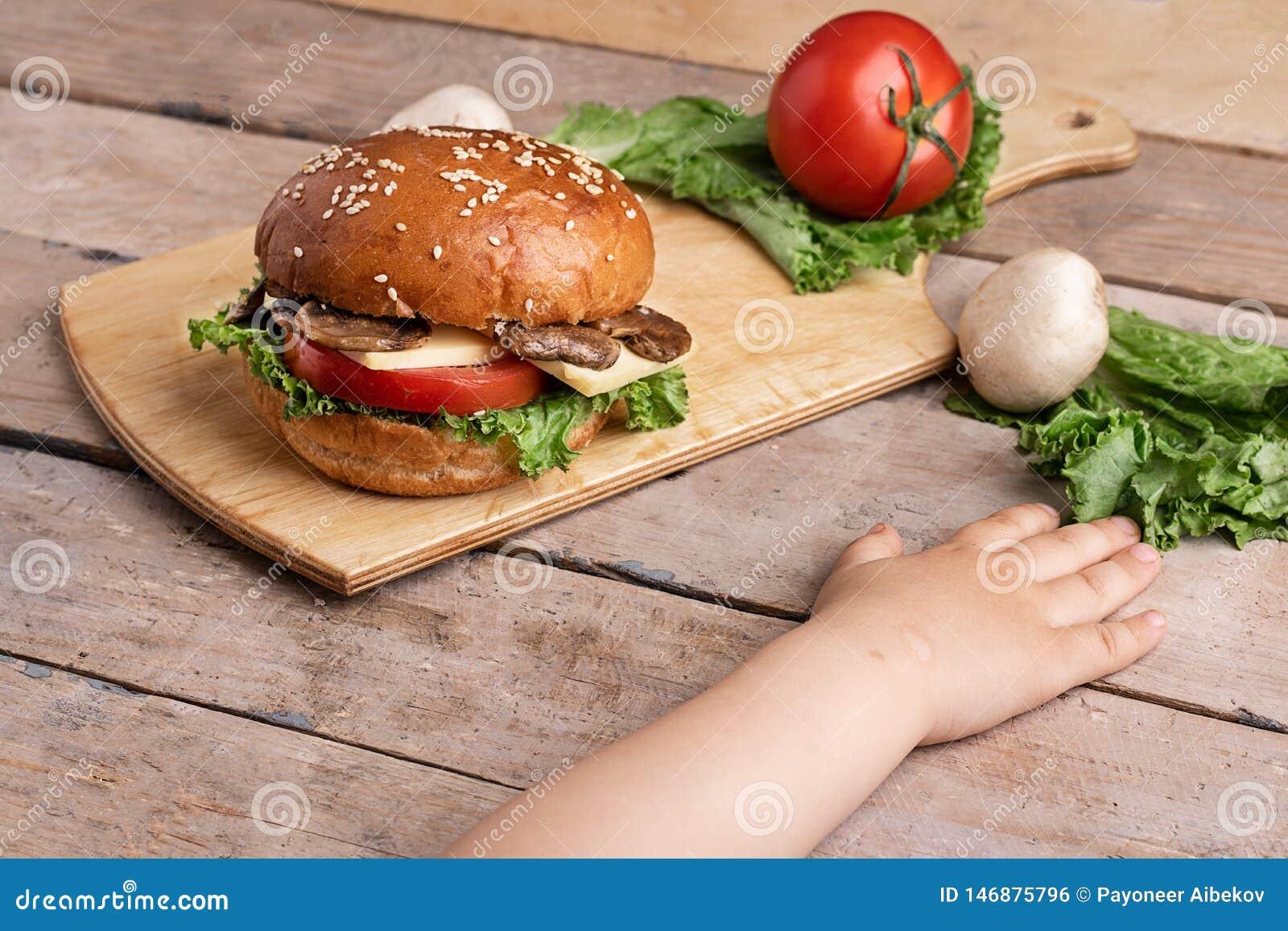 在蘑菇汉堡附近的女孩手用乳酪和蕃茄、未加工的蘑菇和莴苣,砧板