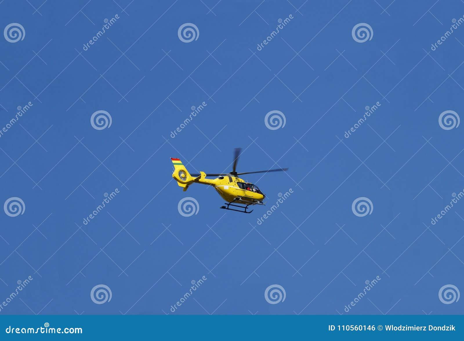 在行动,反对晴朗的天空的飞行的黄色抢救直升机