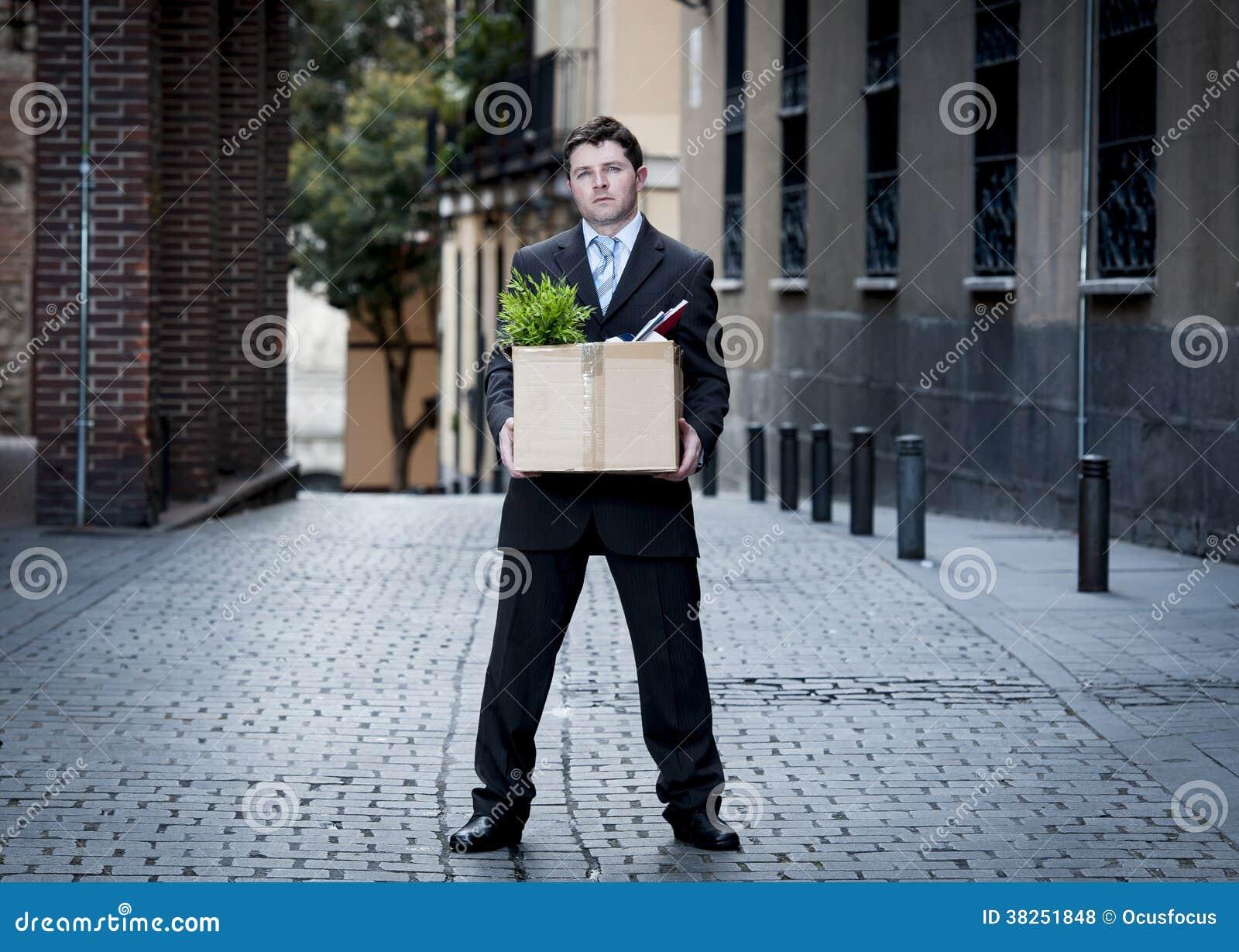 在街道上的沮丧的商人射击了运载的纸板箱