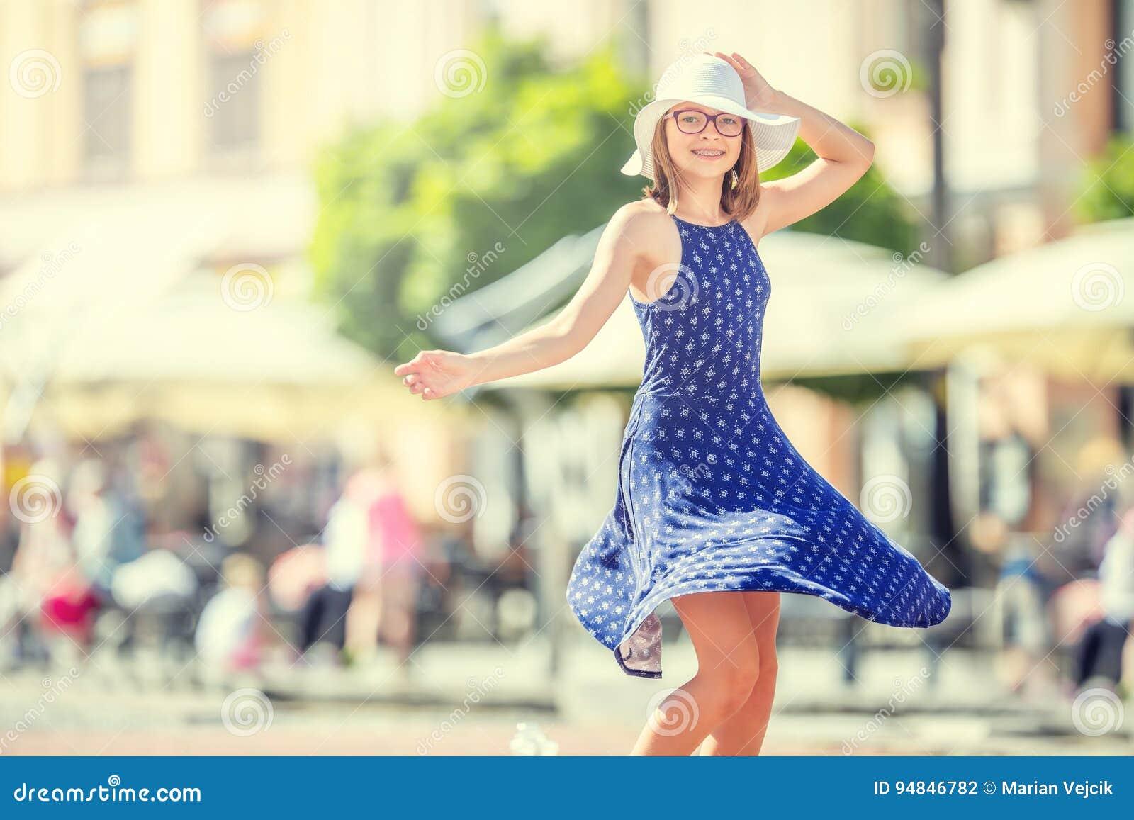 在街道上的美好的逗人喜爱的女孩跳舞从幸福 逗人喜爱的愉快的女孩在夏天给跳舞穿衣在阳光下