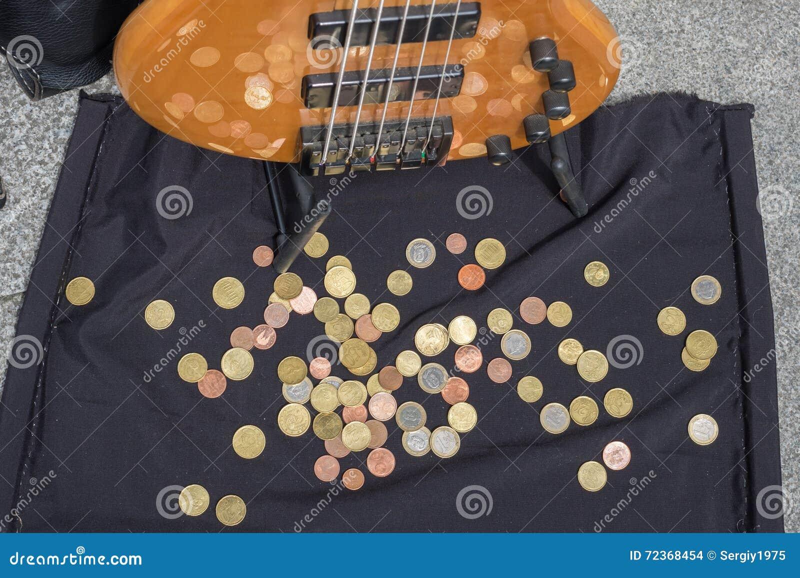 在街道音乐家的吉他的附近硬币