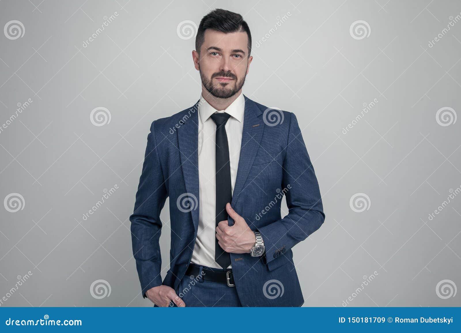 在衣服打扮的一个迷人的成熟的商业人的画象摆在,当站立和看照相机被隔绝在灰色时