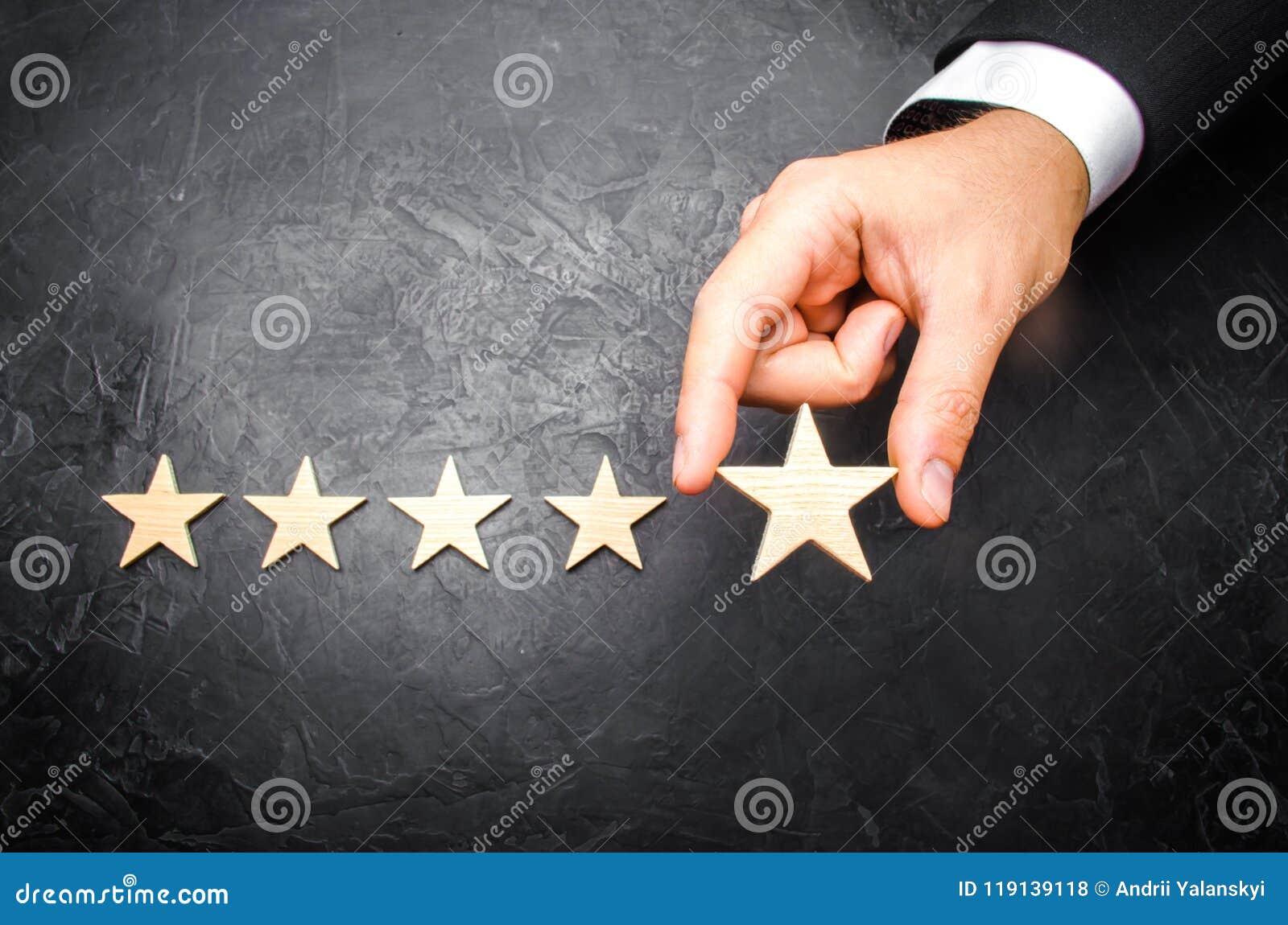 在衣服的商人` s手拿着第五个星 得到第五个星 旅馆和餐馆规定值的概念,