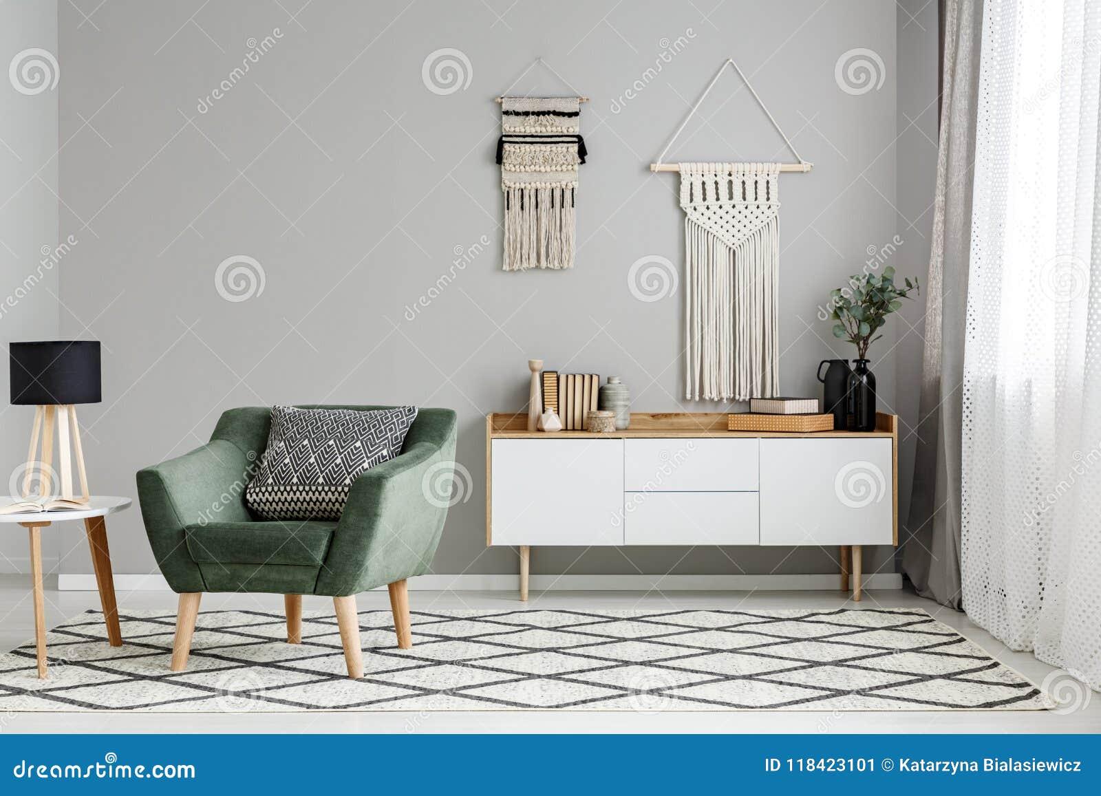 在被仿造的地毯的绿色扶手椅子在与灯的桌附近在minim