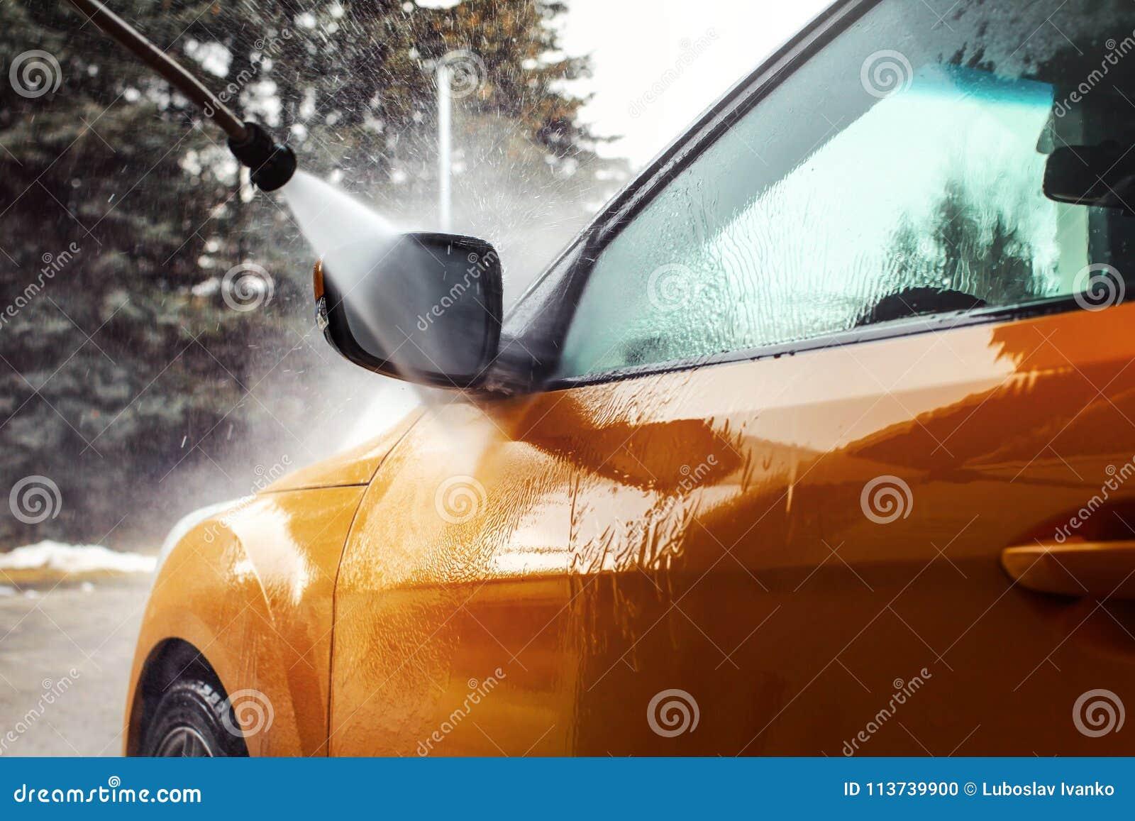 在被洗涤与喷气机wat的黑暗的黄色汽车前面镜子的细节